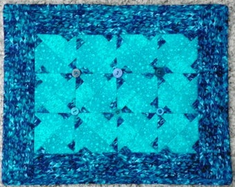 Ice crystals in miniature blue quilt wall hangings.