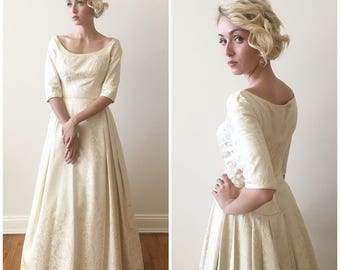 Vintage 1960s Brocade Wedding Gown with quarter length sleeves and scoop waist details.
