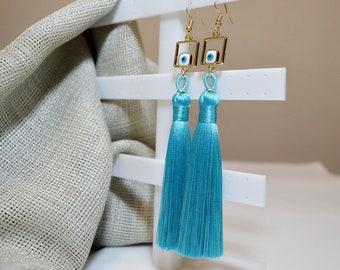 Light blue long soft shiny tassels with enamel glass square evil eye in gold metallic base