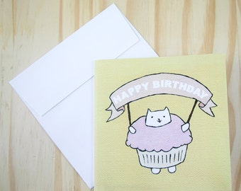 "CARD: ""Cupcake Cat"" featuring a cat in a stupidly cute cupcake suit, holding a Happy Birthday banner"