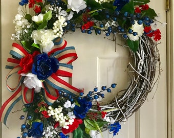 Stars and Stripes-whitewashed grapevine wreath with red, white and blue flowers, and patriotic bow.