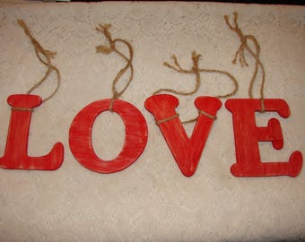 """Red Wood Letters That Spell """"Love"""" With Jute String For Hanging"""