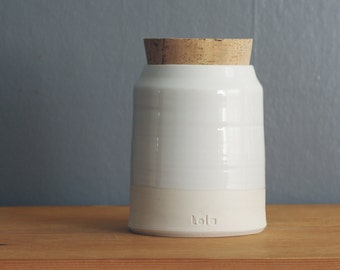 Custom urn for human ashes. Modern pottery funeral cremation urn. shown in white on porcelain. handmade pottery urn