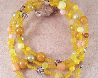 Very long yellow scrap chain made of glass and wax beads