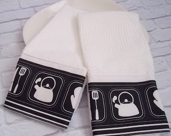 A Set of 2 Gourmet Kitchen Towels, trimmed with screen printed teapots and cooking utensils  and oven mitts.