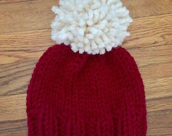 Deep red knit hat with cream Pom Pom