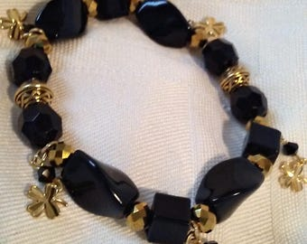 Lucky charms on black and gold stretch bracelet with antique gold plated Celtic knot beads.