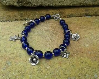 Blue glass bracelet with flower charms.