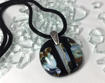 fused glass pendant with a mix of light blue, silver, caramel and iridescent white on black