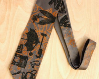 Hand printed Silk Necktie in warm gray silk with vintage imagery in orange and black, original and one of a kind