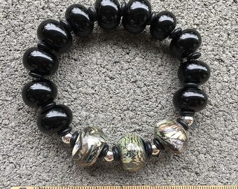 """Unique handmade lampwork artisan glass bead bracelet with glossy black and green """"silver glass"""" beads from """"worlds within worlds"""" series."""