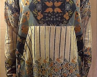 One-of-a-kind 100% up-cycled silk multi-patterned tunic featuring over-sized cowl neck and front pocket detail