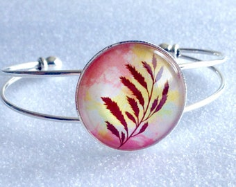 Rigid silver metal and glass cabochon bracelet on pink yellow autumn leaf