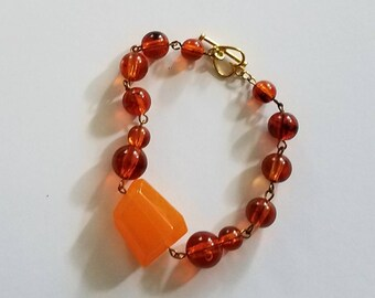 SALE. Bracelet. Asymmetrical orange focal and honey acrylic linked beads. Gold tone heart and bar clasp. Free Shipping.