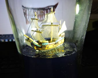 Ship in a bottle, from the age of discovery, sailing on a blue sea