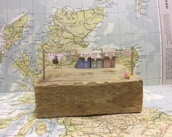 Handmade wooden houses sat on reclaimed wood