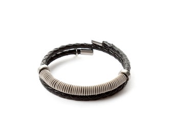 Leather wraparound bracelet with guitar string coil