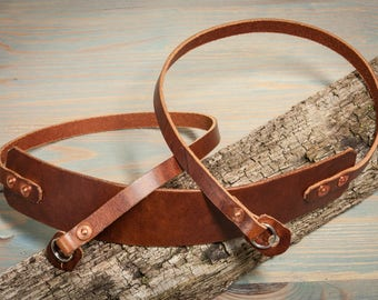 Chesnut leather copper riveted camera strap with fixed shoulder pad.