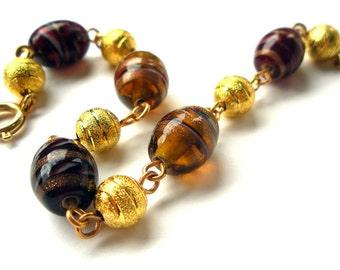 La main Stardust or Bracelet avec or rouge et perles de verre ambre Swirl