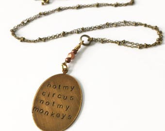 Not my circus not my monkeys necklace in bronze with faceted detail