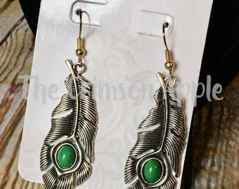 Silver tone feather earrings with green stones