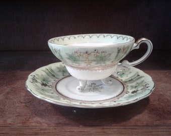 Teacup and saucer grean and gold detail