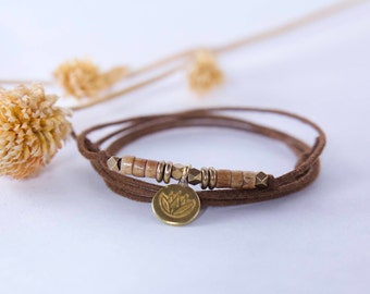 Brass Lotus with bone beads on a waxed cotton cord necklace. Wear 4 ways.