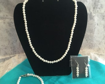 Traditional imitation white pearl necklace set.