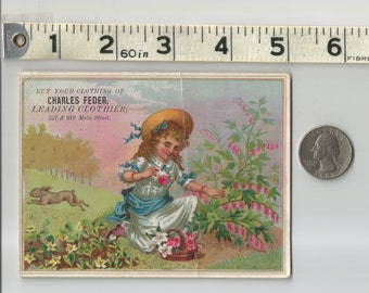 Victorian 1880s Trade Card Charles Feder Clothier Paterson NJ Pretty girl in lovely dress & hat in bright garden with flowers and rabbit