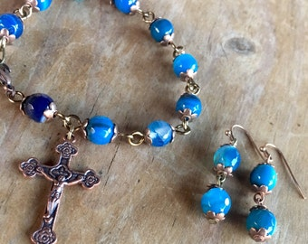 Handmade bracelet with semi-precious agate gemstone beads in shades of blue with tibetan copper crucifix and matching earrings