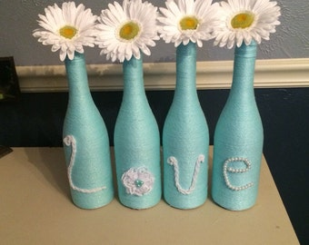 Shimmery Aqua Wine Bottles with Gerber Daisies that Spell Love