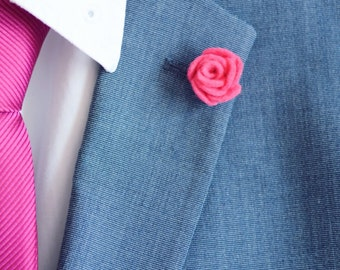 A small pink 2cm lapel flower pin that's is favoured for modern office wear for it's size