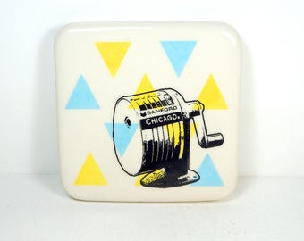 tile with yellow & blue triangles and a Chicago pencil sharpener, ready to ship