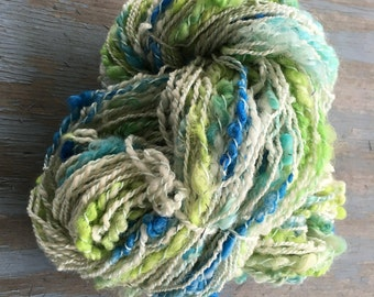 Handspun Shetland Yarn with dyed locks and cotton trim. 4 ounces of thick and thin.