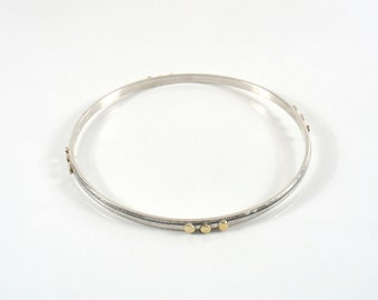 twelve yellow gold dots decorate this stripes silver bangle.Delicate and elegant silver bangle.