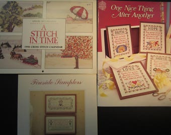 3 cross stitch pattern booklets, 1990 calender with 12 nice scenes with sayings,Faith, Hope, Love sayings, Baby and fireside sampler,Family