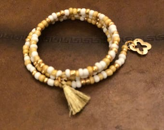 Wrap bracelet, gold and white colored beads with tassel and gold charm