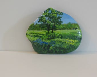 Hand painted rock of trees and a spring meadow.