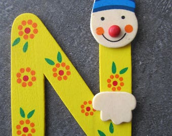 "Painted wood - representing the letter ""N"" in the form of a clown"