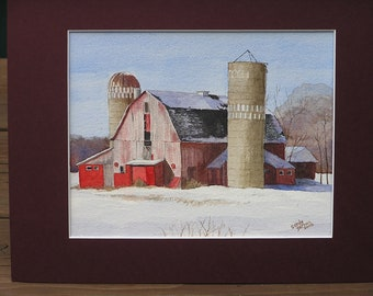 Red barn and two silos in Winter.