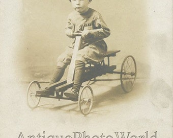 Cute child on amazing toy car antique rppc photo