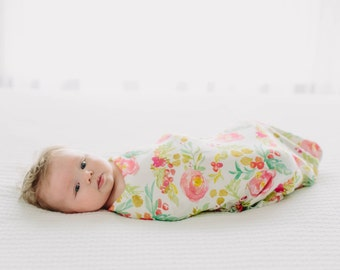 Organic cotton swaddle blanket in winter floral with pink flowers and gold accents, holly, laurels