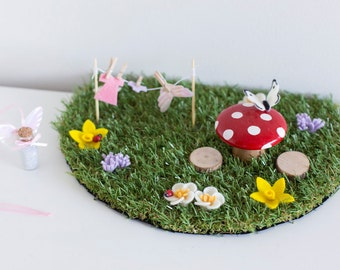 Fairy garden display mat for fairy door including grass mat, toadstool table and wooden stools, fairy clothes line and felt flowers.