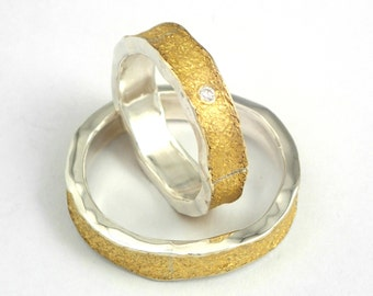 Modern two tone wedding bands with glossy silver and a sandy-rough 22K gold surface. Woman's ring has a discreet small loose diamond.