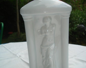 White porcelain bottle with a feminine sculpture. Bottle in white porcelain with a sculpture of a woman.