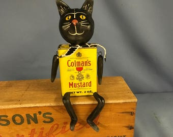 Paper clay sculpted cat figure assembled using a vintage spice tin