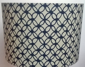 Handmade drum lampshade with repeated cream and navy blue, macrame inspired, circular geometric pattern