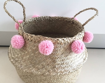 Small wicker basket with pink pompoms