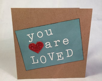 Square kraft card stating YOU ARE LOVED with a red glitter heart