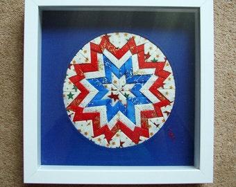 Patchwork textile art framed in white box frame.